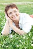 Mujer atractiva 50 años en el parque con un teléfono móvil Fotografía de archivo