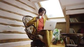 Mujer atractiva adulta en vidrios que mira película en el ordenador portátil y que bebe el café en ático almacen de metraje de vídeo