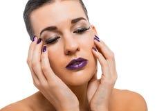 Mujer atractiva agraciada con los labios y los clavos púrpuras fotos de archivo