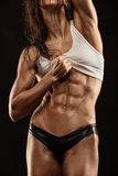 Mujer atractiva agradable de la aptitud que muestra los músculos abdominales fotografía de archivo