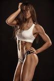 Mujer atractiva agradable de la aptitud que muestra los músculos abdominales Fotos de archivo