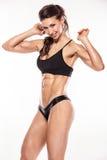 Mujer atractiva agradable de la aptitud que muestra los músculos abdominales imagen de archivo