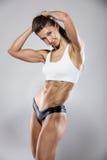 Mujer atractiva agradable de la aptitud que muestra los músculos abdominales Fotografía de archivo libre de regalías
