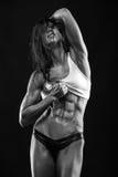 Mujer atractiva agradable de la aptitud que muestra los músculos abdominales imagenes de archivo