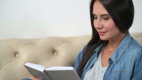 Mujer atractiva agradable que lee un libro en casa metrajes