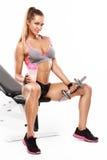 Mujer atractiva agradable que se sienta en un banco y un entrenamiento con pesa de gimnasia Imagenes de archivo