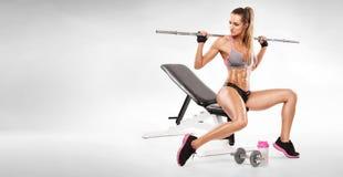 Mujer atractiva agradable que se sienta en un banco y un entrenamiento con pesa de gimnasia Imagen de archivo libre de regalías