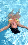 Mujer atractiva, apta que flota en piscina Fotos de archivo libres de regalías