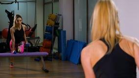 Mujer atractiva apta que se resuelve en pesas de gimnasia de elevación del dispositivo de ejercicio almacen de video