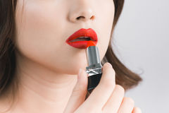 Mujer atractiva asiática joven con el pelo oscuro usando el lápiz labial rojo Imagen de archivo