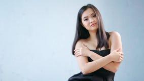 Mujer atractiva asiática sonriente del tiro medio que lleva la pequeña situación negra del vestido con las manos cruzadas almacen de video