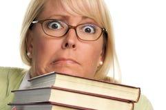 Mujer atractiva asustada con la pila de libros imagen de archivo