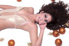 Mujer atractiva atractiva con el bikini que miente, bolas del oro del brillo de la Navidad alrededor de ella Imagen de archivo libre de regalías