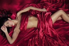 Mujer atractiva bajo las hojas del satén Imagen de archivo libre de regalías
