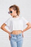 Mujer atractiva bastante joven de la moda que presenta en la pared de ladrillo blanca Fotografía de archivo libre de regalías