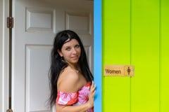 Mujer atractiva bastante sonriente en una puerta de entrada imagenes de archivo