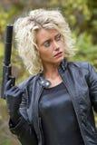 Mujer atractiva con el arma del silenciador Foto de archivo