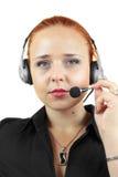 Mujer atractiva con el auricular en el fondo blanco Imagen de archivo libre de regalías