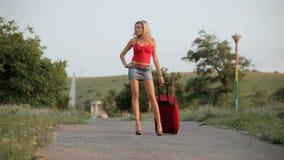 Mujer atractiva con el bolso que camina en el camino metrajes