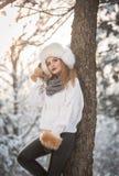 Mujer atractiva con el casquillo y la chaqueta blancos de la piel que disfruta del invierno Vista lateral de la presentación rubi imagen de archivo