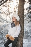 Mujer atractiva con el casquillo y la chaqueta blancos de la piel que disfruta del invierno Vista lateral de la presentación rubi imágenes de archivo libres de regalías