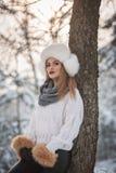 Mujer atractiva con el casquillo y la chaqueta blancos de la piel que disfruta del invierno Vista lateral de la presentación rubi imagenes de archivo