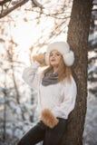 Mujer atractiva con el casquillo y la chaqueta blancos de la piel que disfruta del invierno Vista lateral de la presentación rubi foto de archivo libre de regalías