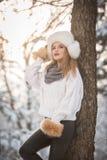 Mujer atractiva con el casquillo y la chaqueta blancos de la piel que disfruta del invierno Vista lateral de la presentación rubi fotos de archivo libres de regalías