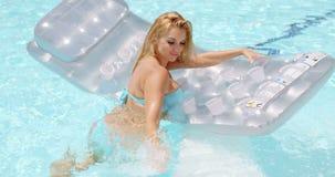 Mujer atractiva con el colchón flotante en la piscina metrajes