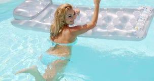 Mujer atractiva con el colchón flotante en la piscina almacen de metraje de vídeo