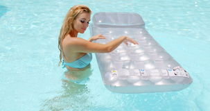 Mujer atractiva con el colchón flotante en la piscina almacen de video