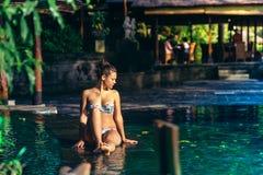 Mujer atractiva con el cuerpo delgado y bien proporcionado bronceado en el bikini colorido, presentando en la piscina del infinit Foto de archivo