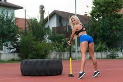 Mujer atractiva con el martillo y el neumático Imagenes de archivo
