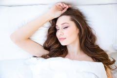 Mujer atractiva con el pelo largo hermoso que duerme en cama Foto de archivo libre de regalías