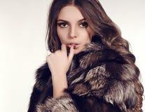 Mujer atractiva con el pelo oscuro en abrigo de pieles lujoso Foto de archivo libre de regalías