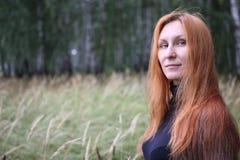 Mujer atractiva con el pelo rojo en el bosque del otoño Foto de archivo