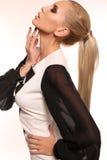 Mujer atractiva con el pelo rubio que lleva el vestido blanco y negro elegante Imagen de archivo libre de regalías