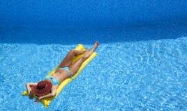 Mujer atractiva con el sunhat que se relaja en colchón neumático imagenes de archivo