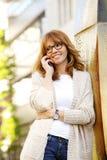 Mujer atractiva con el teléfono elegante Fotos de archivo