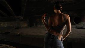 Mujer atractiva con el top marrón y vaqueros que bailan en la oscuridad metrajes