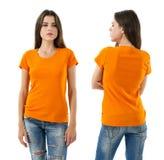 Mujer atractiva con la camisa anaranjada en blanco y vaqueros Imagenes de archivo