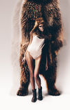 Mujer atractiva con la capilla de la piel en la cabeza con el oso detrás Fotografía de archivo libre de regalías