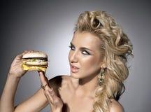 Mujer atractiva con la hamburguesa imagen de archivo