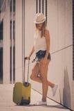 Mujer atractiva con la maleta que se relaja después de llegada Fotos de archivo libres de regalías