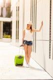 Mujer atractiva con la maleta que se relaja después de llegada Fotografía de archivo
