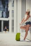 Mujer atractiva con la maleta que se relaja después de llegada Imagen de archivo