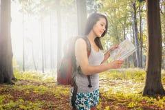 Mujer atractiva con la mochila perdida en bosque Fotos de archivo