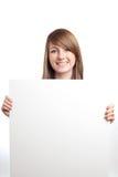 Mujer atractiva con la muestra en blanco. Sonrisa. Fotos de archivo