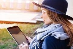 Mujer atractiva con la tableta digital a disposición que habla en el teléfono móvil con el bpyfriend antes de una reunión con ell Imagen de archivo libre de regalías