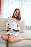 Mujer atractiva con la tableta en casa imagenes de archivo
